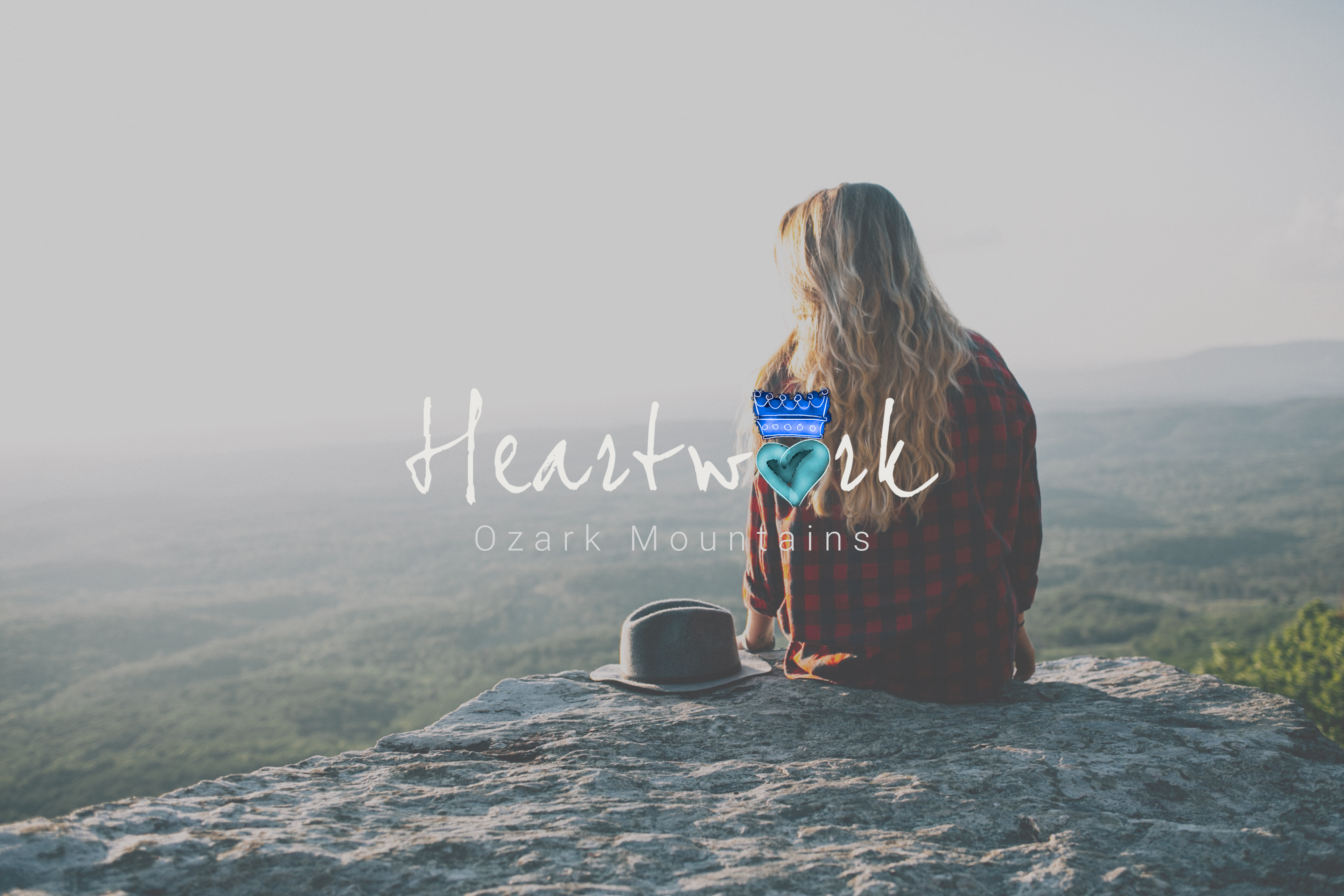 Heartwork Logo over picture of a woman sitting near the edge of a cliff